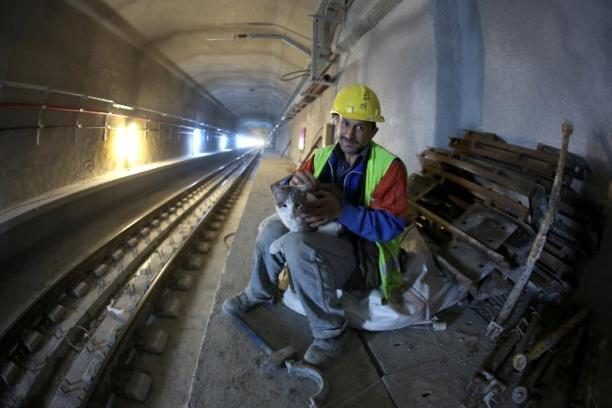 A worker holds a cat in the Marmaray Tunnel under the Bosphorous