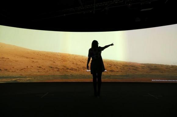 Jacqueline Storey, a press officer at the National Maritime Museum, poses for a photograph in front of images of Mars generated by NASA's Curiosity Rover at their new Visions of the Universe exhibition, in Greenwich, London